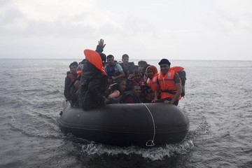 Afghan refugees arrive on an overcrowded dinghy under heavy rainfall on the Greek island of Lesbos after crossing a part of the Aegean Sea from the Turkish coast