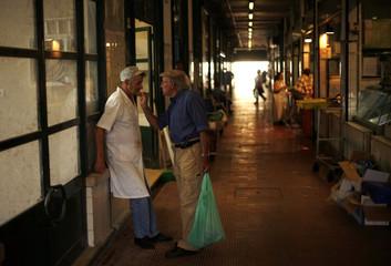 Men speak at the Ribeira market in Lisbon