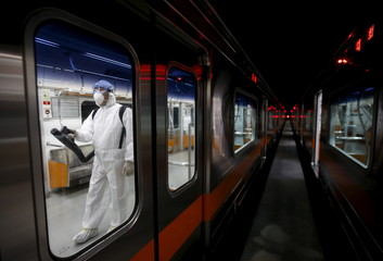 A worker in full protective gear disinfects the interior of a subway train at a Seoul Metro's railway vehicle base in Goyang