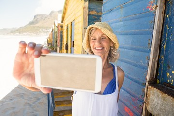 Smiling woman holding phone while standing against wall