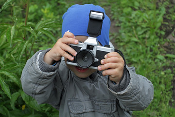 A little boy in a jacket and a blue hat takes pictures of the photographer. Young photographer at work. The kid looks through the lens to the camera