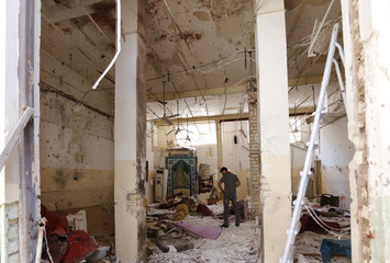 A man walks among debris in a Shi'ite mosque after a bomb attack in Baghdad