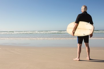 Senior man with surfboard standing on sand