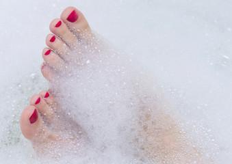 Female feet in soap bath.