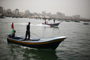 Palestinian fishermen travel on fishing boats as they take part in a protest calling for an increased fishing zone, at the seaport of Gaza City