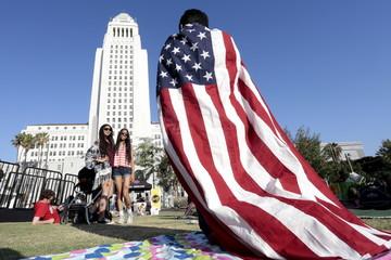 Zain Delawalla, draped in a U.S. flag, takes a photo of Inara Khakwani and Hijab Gulwani during an Independence Day celebration in Los Angeles, California