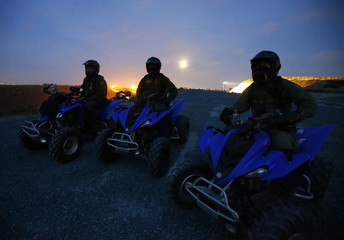U.S. Border Patrol agents  Jarrod Yackel, Manny Villalobos, and David Faatoalia sit on their ATVs atop a hill overlooking Tijuana, Mexico as the moon rises on their night patrol along the international border between Mexico and the United States