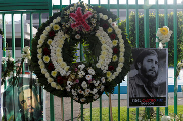 A wreath is seen between pictures of Fidel Castro during a tribute ceremony in Mexico City