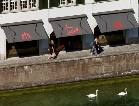 People walk past a shop of French shoe designer Christian Louboutin in Zurich