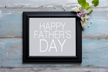 Picture frame with lilac flowers and Happy Father's day message on blue wooden background