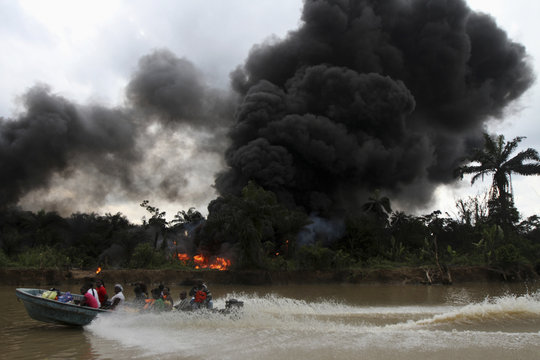 A passenger speedboat churns up the water, while in the background an illegal oil refinery is left burning