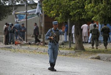 An Afghan policeman keeps watch at the site of suicide bomb attack in Kabul