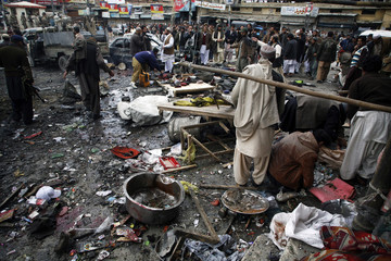 Police officials search for evidences at the scene of a bomb explosion in Quetta