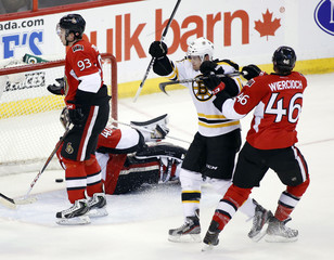 The Boston Bruins Daniel Paille reacts after scoring the Bruins first goal of the game on the Ottawa Senators goaltender Robin Lehner as the Senators Mika Zibanejad and Patrick Wiercioch skate by during the second period of their NHL hockey game at Scotiab