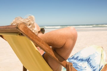 Side view of senior woman relaxing on chair against clear sky