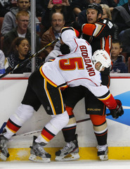 Anaheim Ducksr Ryan Getzlaf  is checked off the puck by Calgary Flames  Mark Giordano  during their NHL hockey game in Anaheim