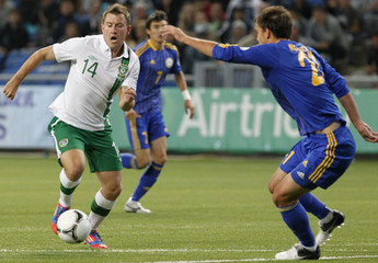Kazakhstan's Rozhkov struggles for the ball with Ireland's Vermouth during their World Cup 2014 qualifying soccer match in Astana