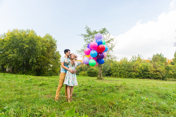 summer holidays, celebration and dating concept - couple with colorful balloons in nature