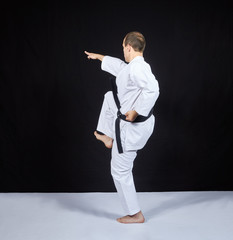 On a black background, a karate athlete beats with a knee