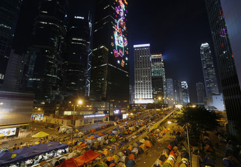 Christmas lights shine on a commercial tower as tents set up by pro-democracy protesters occupy a main road leading to the financial Central district (background) in Hong Kong