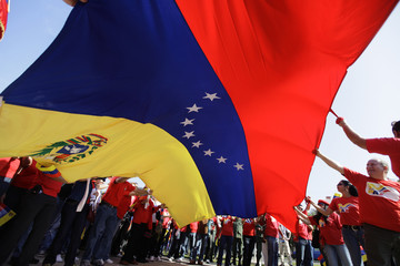 Supporters of Venezuela's President Hugo Chavez wave their national flag during a march marking the 12th year anniversary of the inauguration of Venezuela's President Hugo Chavez in Havana