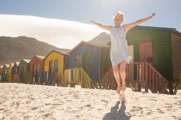 Happy woman jumping on sand against huts