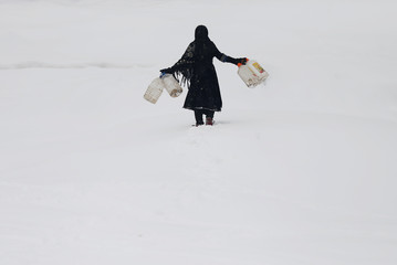 An Afghan girl carries empty water containers during a snowfall in Kabul, Afghanistan