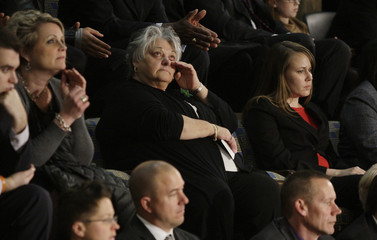 A woman in the House gallery cries during President Obama's discussion of gun control legislation while delivering his State of the Union Speech on Capitol Hill in Washington