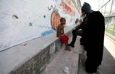 An anti-government demonstrator talks with a boy during a protest at the Jacarezinho slum in Rio de Janeiro