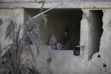 Palestinians inspect their house that witnesses said was damaged during an Israeli airstrike in Gaza City