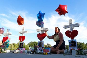A woman poses for a photo in front of a row of 49 wood crosses commemorating the victims of the Pulse night club shooting in Orlando