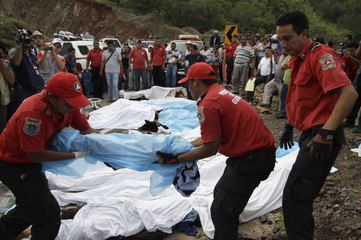 Members of a rescue team carry a dead body next to the site of a passenger bus crash on a wet road in the southwestern state of Guerrero