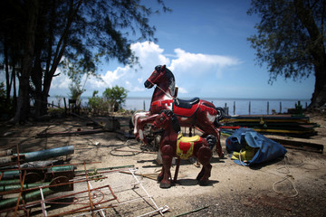 Toy horses used in a playground are seen at the seafront after the passage of waterspouts at the beach town of Playa Caimito in Cuba