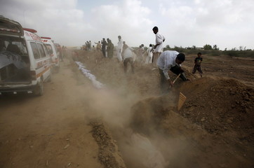 Volunteers bury bodies of people who died due to an intense heat wave, during a mass burial at Edhi Foundation graveyard in Karachi