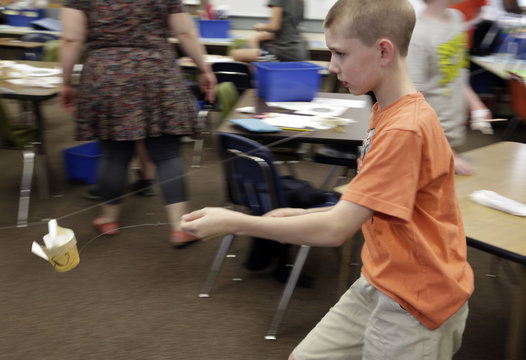 Sixth-grade student Raabe tries out his group's design for a cup that drops a marble on a target via a zip-line as Boeing employees mentor students at after-school STEM academy held at Crestwood Elementary School in Covington, Washington