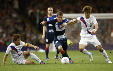 Britain's Ramsey is challenged by South Korea's Ki and Koo in their men's quarter final soccer match at the London 2012 Olympic Games at Millennium Stadium in Cardiff
