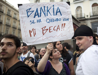 """A demonstrator holds up a signe during  a protest marking the first anniversary of the 15M """"Indignados"""" (Indignant) movement"""