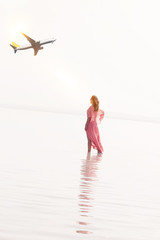 woman stand looking passenger airplane landing on the tropical beach . Ready for Summer Travel, sun and airplane