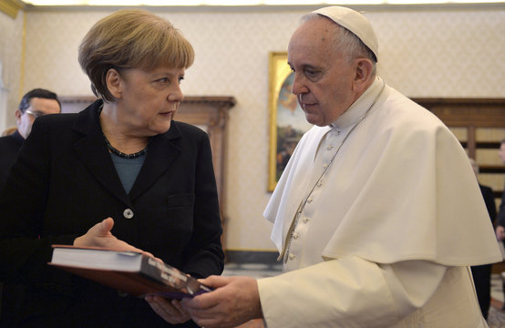 German Chancellor Angela Merkel exchanges gifts with Pope Francis during a private audience at the Vatican