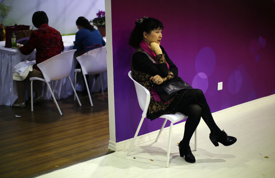 A woman sits during a government-sponsored matchmaking event for middle-aged singles and seniors in Shanghai