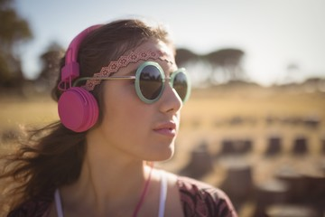 Young woman listening music while wearing sunglasses