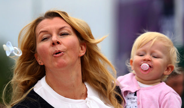 An unidentified participant holds her baby as she takes part in the women's final of the pacifier spitting World Championship in Nidderau near Frankfurt