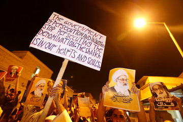 "A protester holds a banner saying ""The government of persecution and injustice. Stop persecuting the denomination. The sheikh is in our hearts and souls"" and photos of Bahrain's leading Shi'ite cleric Isa Qassim shout religious slogans during a sit-in outs"