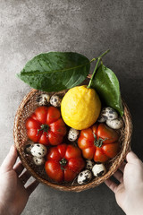 Organic products in a wicker basket. Fresh ripe tomatoes and quail eggs and lemon with leaves. healthy harvest