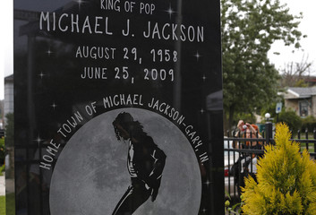 A monument for late musician Michael Jackson is pictured as a fan takes pictures of his childhood home in Gary, Indiana