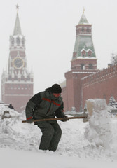 A worker removes snow near Red Square, with the Kremlin wall seen in the background, during heavy snowfall in central Moscow