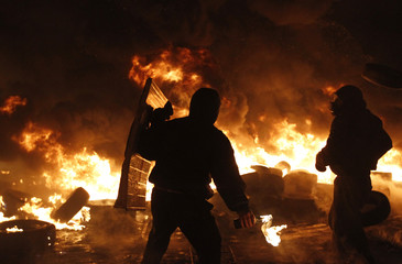 Anti-government protester throws molotov cocktails at the site of clashes with riot police in Kiev