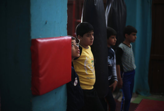 Palestinian boys watch as others participate during a class at the Red Dragon martial arts club in Beit Lahiya