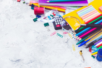 School supplies: colored pencils wooden yardstick erasers binders stationery gum paper clips pencil sharpener a small clothespin colored pins pencil and pen isolated on white background