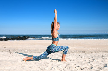 Yoga outdoors - woman practicing yoga at beach
